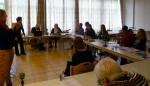 Teilnehmer sitzen in U-Form am Tisch, Referentin und die Teilnehmer hören einem Teilnehmer zu, wie er von einer Situation berichtet, zu der er eine Frage hat. Im Vordergrund sind zwei Gebärdensprachdolmetscherinnen.